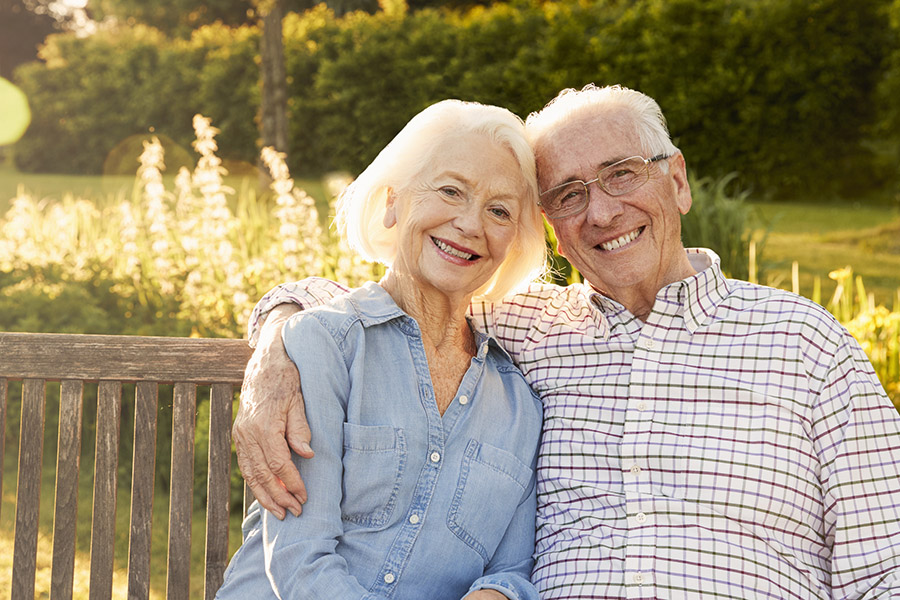Senior Couple Sitting On Garden Bench In Evening Sunlight