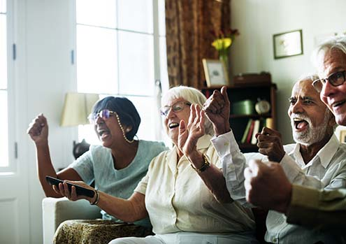 Senior people watching television together